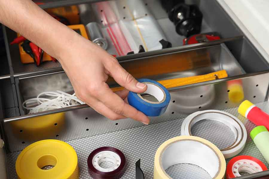 Hand taking adhesive tape from drawer